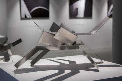 Front: Riccardo Murelli (b. 1975) Costruzione project, 2015 Unlimited Stainless steel 80 х 70 х 40 cm Background: Mikhail Rozanov (b. 1973) Costruzione project, 2015 Geometry series С-print 70 х 105 cm © Ruarts Gallery